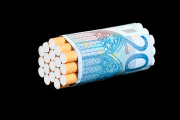 Cigarettes and money on a black background. No smoking concept.