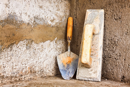 Trowels and masonry tools on a rough concrete wall