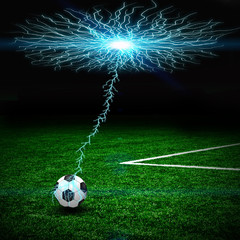 Soccer ball on the green field and lightning