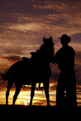 Fototapete - Cowboy holding horse in sunset
