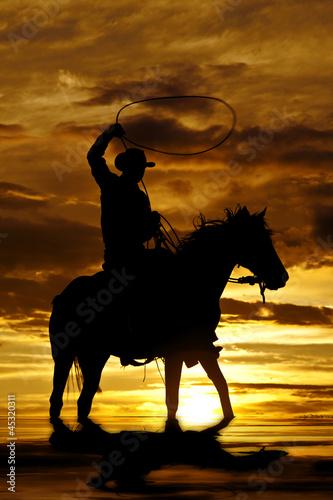 Fototapete Cowboy swinging rope on horse in water