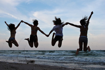 Group of happy women jump on the beach