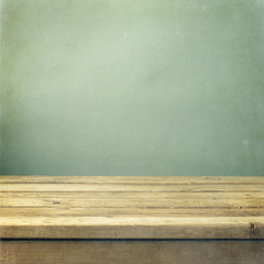 Wooden deck table on green grunge background