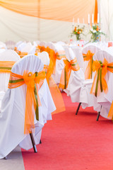 orange wedding chairs with silk ribbons
