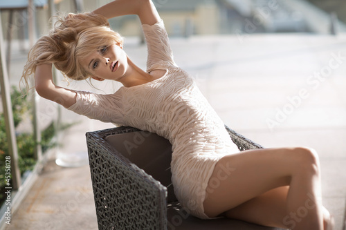Худощавая европейка раздевается у плетённого кресла  315223