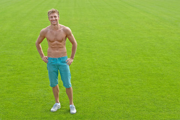 Fit young man on green playing field