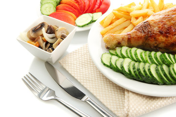 Roast chicken with french fries and sliced vegetables
