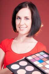 Beautiful young woman holding different makeup shadow and rouge