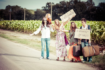 Hippie Group Hitchhiking on a Countryside Road