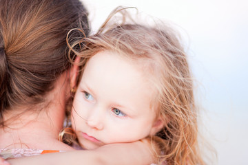 Little girl held by her mother