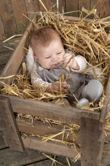 baby in crate with straw