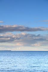 cloudy blue sky leaving for horizon blue surface sea