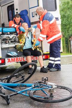 Emergency paramedics helping woman bike accident
