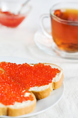 Red caviar on a slice of bread and tea
