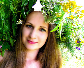 A girl in a wreath of flowers and herbs