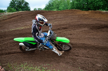MX rider turns on a dirt hill