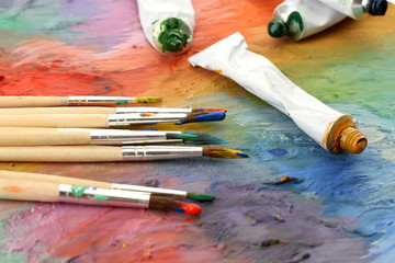 acrylic paint, paint tubes and brushes on wooden palette