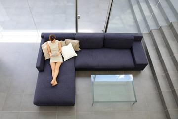 タブレットを持ってソファで寛ぐ女性