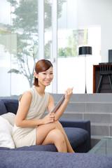 タブレットPCをソファに座って使う女性
