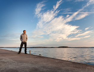 Man stands on the concrete pier starring at the sea