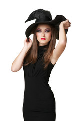 beautiful witch holds a hat
