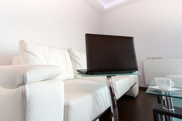 Modern living room with white leather sofa and laptop