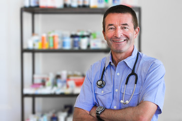 Mature Doctor Standing In Front Of Medicine