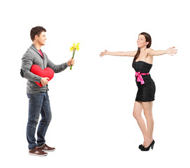 Man giving a red heart and flowers to his girlfriend