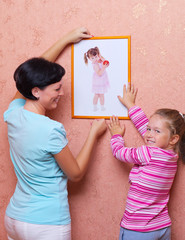 Young woman with girl hanging up a picture
