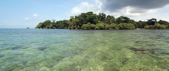 Panorama on shallow waters with a tropical island
