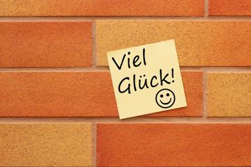Wand mit einem gelben Zettel und Viel Glück