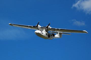 Seaplane Catalina in flight on blue sky