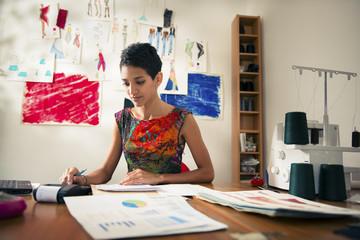 Obraz hispanic woman doing budget in fashion designer atelier - fototapety do salonu