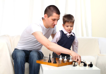Father and son playing chess on sofa