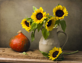 Still life with sunflower bouquet and pumpkin on wooden table
