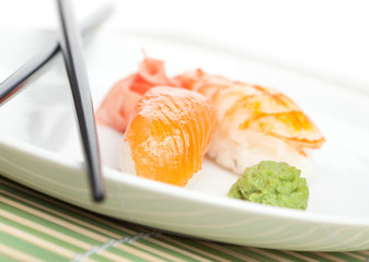 Taking nigiri sushi from the plate with chopsticks