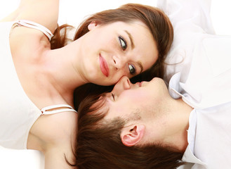 A young couple lying, looking at each other, isolated on white