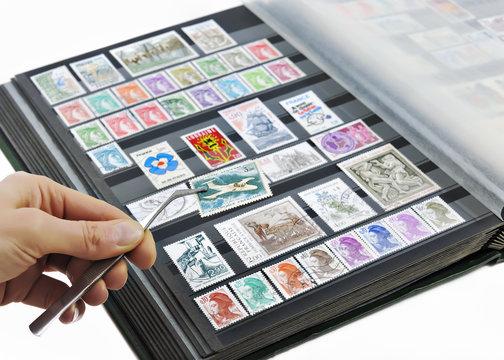 Hand holding postage stamp with tweezers over album