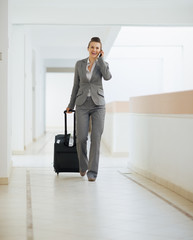 Business woman in business trip walking with wheel bag and speak