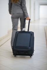 Closeup on business woman walking with wheel bag