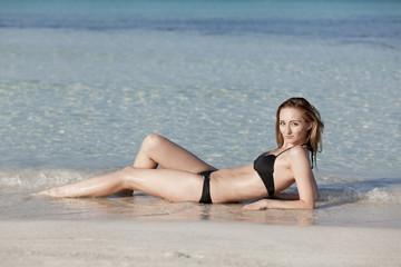 Junge Frau mit schwarzem Bikini am Strand im Wasser Querformat