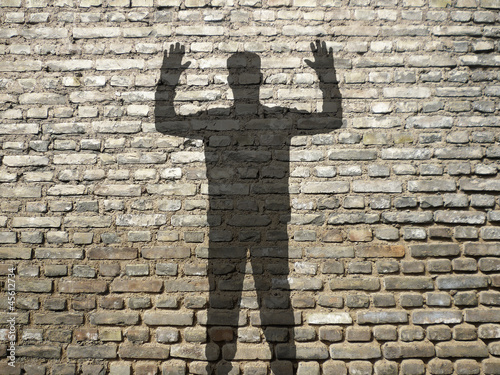 ombre d 39 homme mains en l 39 air sur mur de briques photo libre de droits sur la banque d 39 images. Black Bedroom Furniture Sets. Home Design Ideas