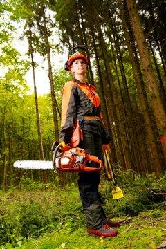 Waldarbeiterin mit Kettensäge in Schutzkleidung