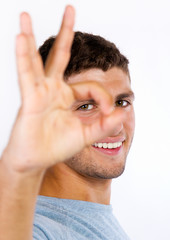 Young man doing the ok sign on white background