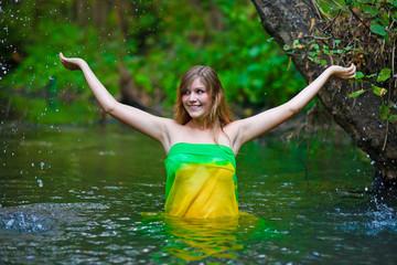Female woman nude model standing under the rain, waist-deep in w