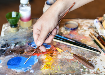 Hand of the artist with a paintbrush