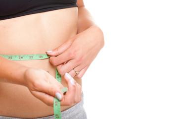woman slim stomach with measuring tape around it