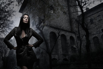 Fashion shoot of a young and sexy brunette in a dark dress