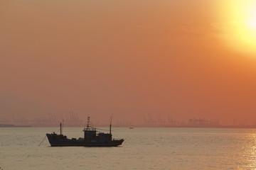 木质渔船在黄昏日落的海洋上