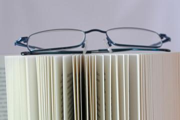 aufgeschlagene buchseiten mit brille